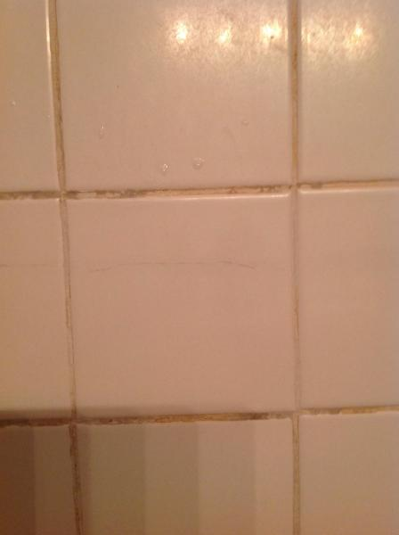 repair   Cracked bathroom tile   runs almost entire length of the         Close view of cracked tiles wall
