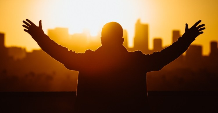 man with hands raised at sunrise over city