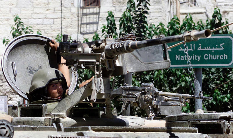 An Israeli soldier close the hatch of his armored personell carrier (APC) during a search in Bethlehem July 8, 2002 near the church of Nativity in Bethlehem (Reuters Photo)