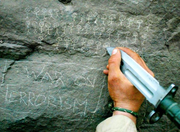 US Army 10th Mountain Division soldier Jorge Avino from Miami, Florida carves the body count that their mortar team has chalked up on a rock, near the villages of Sherkhankheyl, Marzak and Bobelkiel, in Afghanistan, March 9, 2002. [Photo: Reuters]
