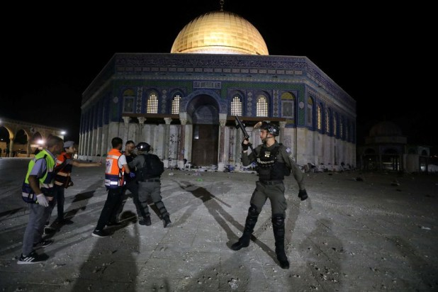 a palestinian hurls stones at israeli police during clashes at the compound that houses al aqsa mosque known to muslims as noble sanctuary and to jews as temple mount amid tension over the possible eviction of several palestinian families from homes on land claimed by jewish settlers in the sheikh jarrah neighbourhood in jerusalem s old city may 7 2021 reuters