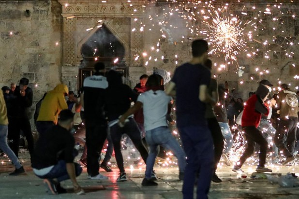 palestinians react as israeli police fire stun grenades during clashes at the compound that houses al aqsa mosque known to muslims as noble sanctuary and to jews as temple mount amid tension over the possible eviction of several palestinian families from homes on land claimed by jewish settlers in the sheikh jarrah neighbourhood in jerusalem s old city may 7 2021 reuters