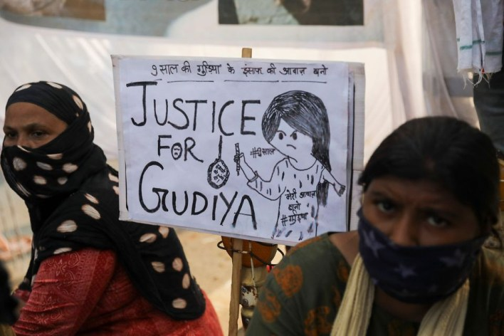 women sit next to a placard near a crematorium where people are protesting against the alleged rape and murder of a 9 year old girl in new delhi india august 5 2021 photo reuters