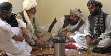 Elders from the Arghandab River Valley talk while waiting for a shura meeting to convene in the district government center March 24.