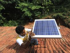 Sharan Pinto installs a solar panel on the rooftop of a house in Nada, a village near Mangalore, India, on May 25.
