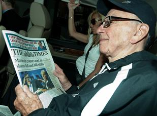 News Corporation Chief Rupert Murdoch reads a copy of the 'London Times' newspaper as he arrives back at his London home on Tuesday.