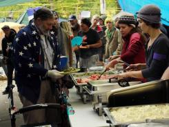 "People line up for free lunch Wednesday at the ""Occupy Portland"" camp in Portland, Ore. ""Occupy Wall Street"" protesters camping out across the country are rubbing shoulders with homeless people."
