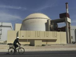 Iran defies international pressure: A worker rides a bike in front of the reactor building of the Bushehr nuclear power plant Oct. 26.