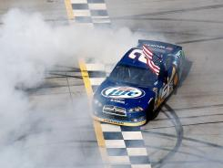 Brad Keselowski does a burnout at Talladega Superspeedway with the American flag flying out his window — his customary victory celebration.