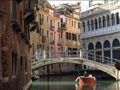 A small boat makes its way down a small canal in Venice, Italy.
