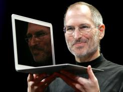 CEO Steve Jobs holds up the new MacBook Air after giving the keynote address at the Apple MacWorld Conference in San Francisco. Apple on Wednesday, Oct. 5, 2011 said Jobs has died.