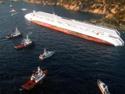 A handout photo taken and released Saturday shows the Costa Concordia cruise ship after it ran aground and keeled over off the coast of Italy.