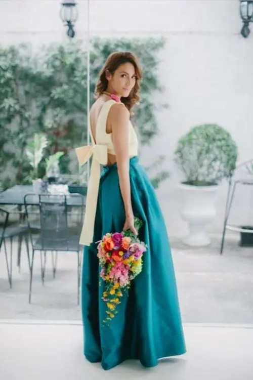 a bold bridesmaid look with a light yellow crop top with a tied back and an emerald full maxi skirt plus a statement necklace