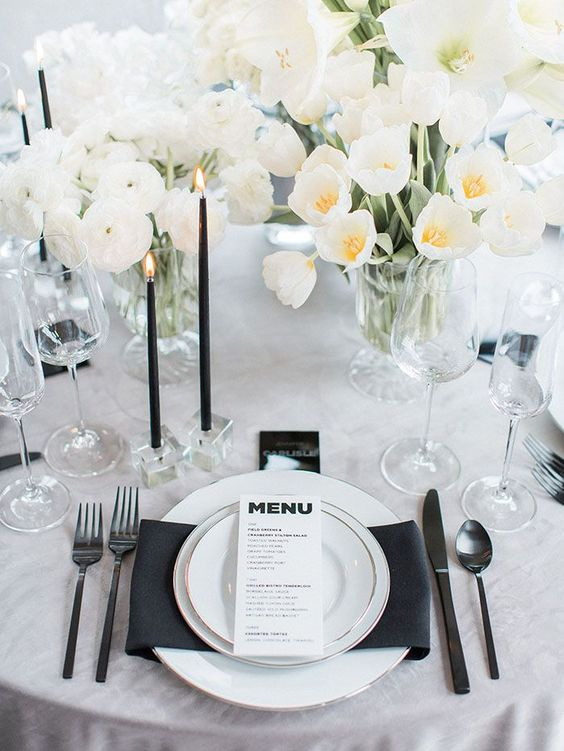 a chic modern black and white wedding tablescape with a black napkin, candles and dark cutlery plus lush white blooms
