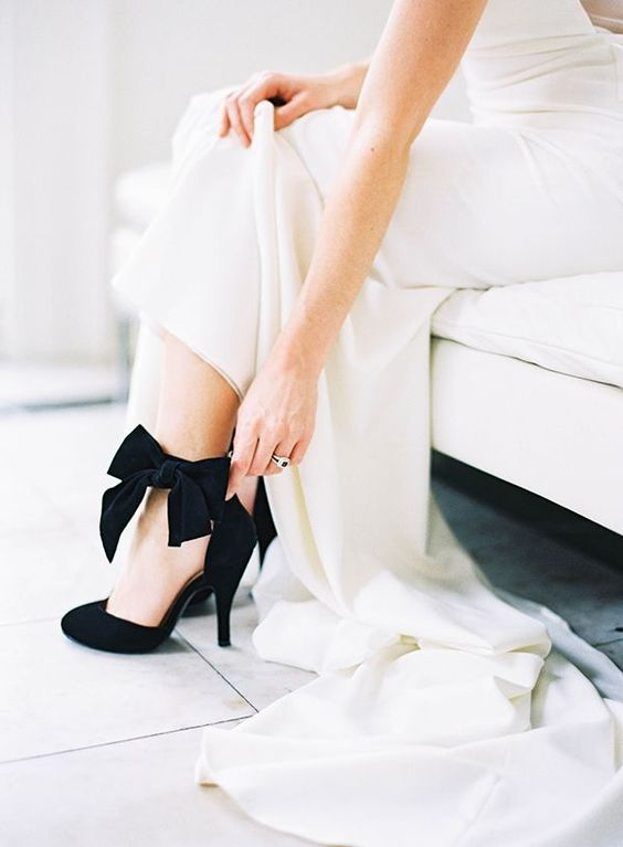 a neutral wedding gown paired with black velvet shoes with bows for a timelessly elegant look