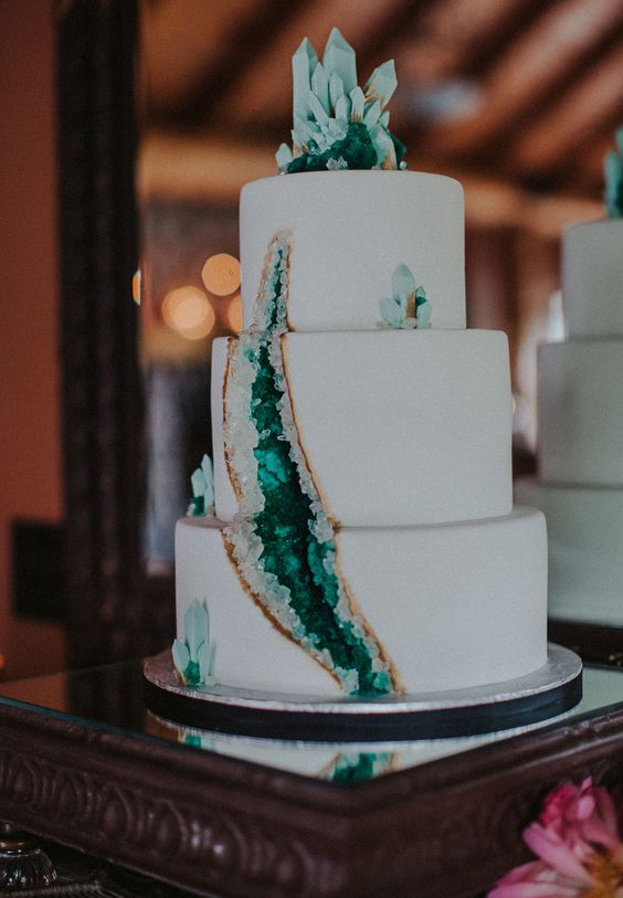 a white wedding cake decorated with emerald geodes is a very edgy idea to try for a modern wedding