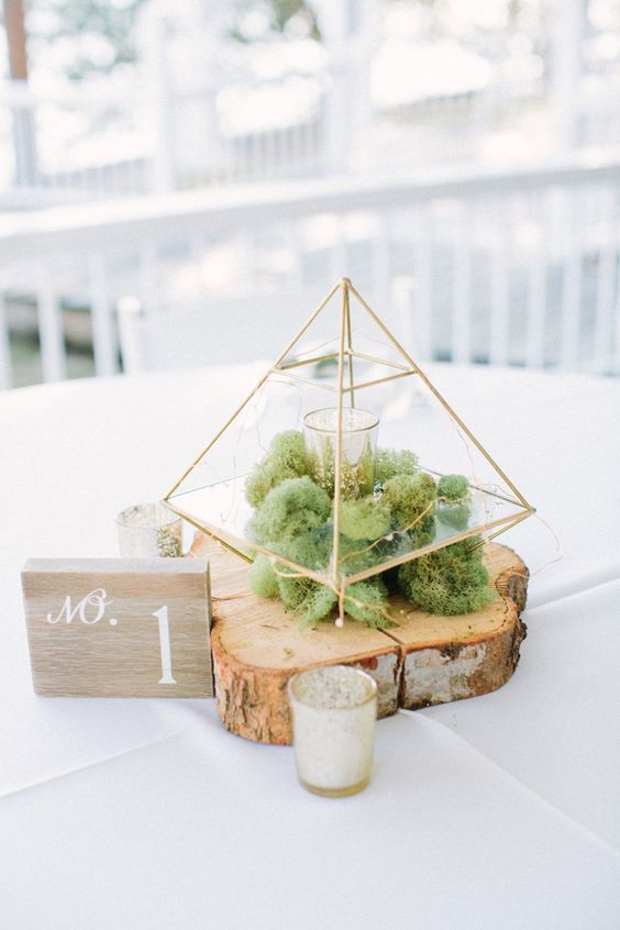 a wooden slice, moss, a terrarium with candles and a wooden table number for a rustic wedding