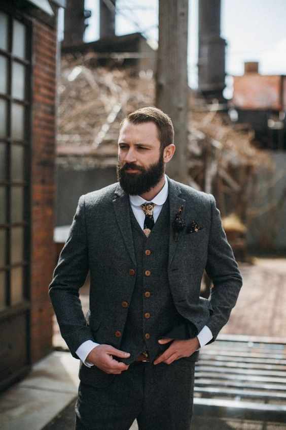 a vintage groom outfit with a grey tweed three-piece suit with copper buttons, a white shirt, a moody floral tie