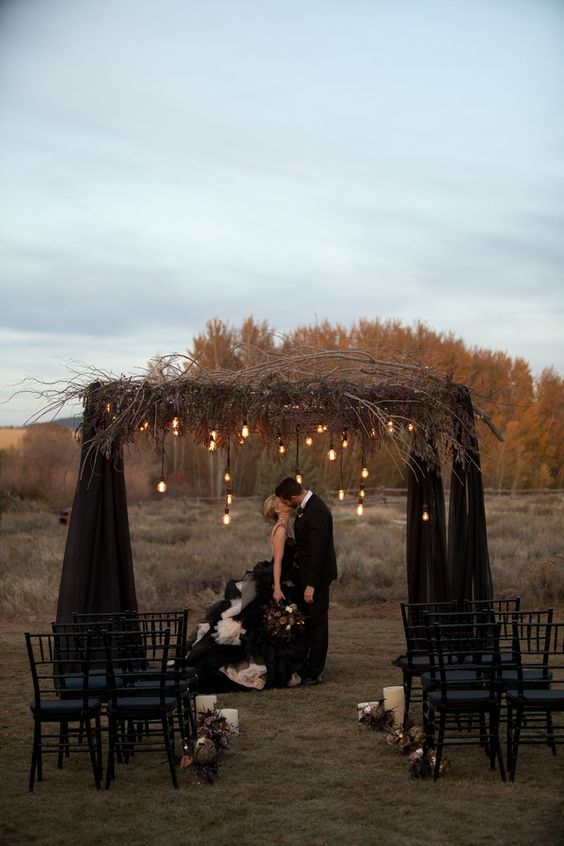 a black wedding arch with fabric, dried branches and bulbs hanging down