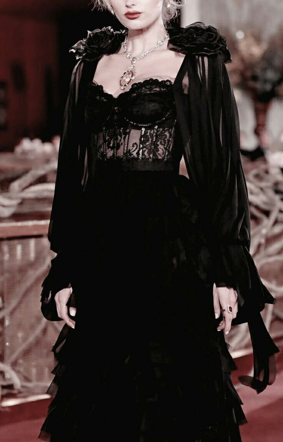 a black wedding dress with a corset, a layered mxi skirt and a black airy cape with fabric flowers