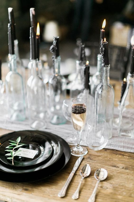 a chic modern gothic table setting with an airy runner, black plates, black candles in bottles