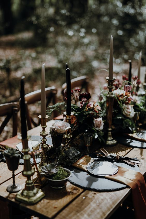 a dark tablescape with an uncovered table, succulents, blooms, greenery and white and black candles