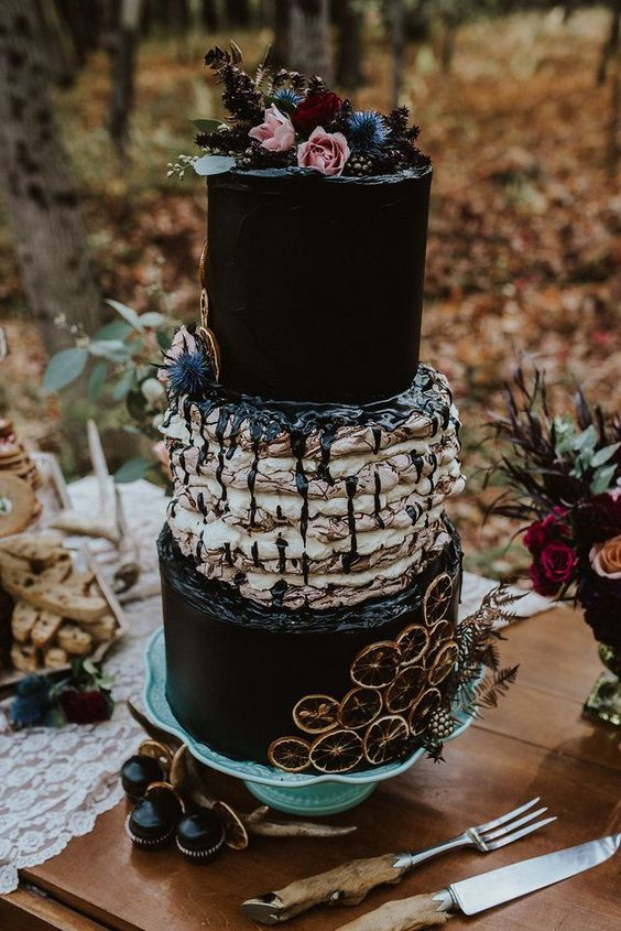 a gothic wedding cake with black and pavlova tiers, fresh blooms and berries on top, chocolate drip and citrus