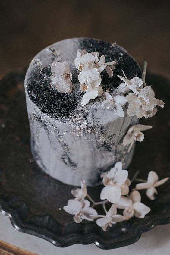 a moody grey wedding cake with black glitter, white blooms on top for a chic touch
