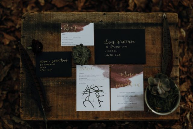 modern and moody wedding invitation suite in black and white, with calligraphy and burgundy watercolor
