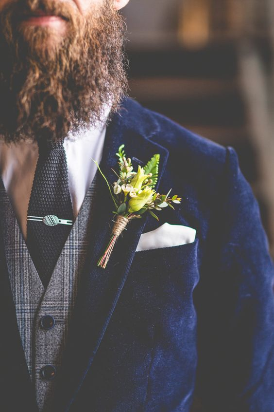 a boho winter groom's look with a navy velvet blazer, a grey checked waistcoat, a black tie and a bright yellow boutonniere