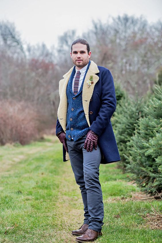a boho winter groom's outfit with a white button down, a striped tie, a blue cardigan, grey pants, brown shoes and a blue coat with faux fur