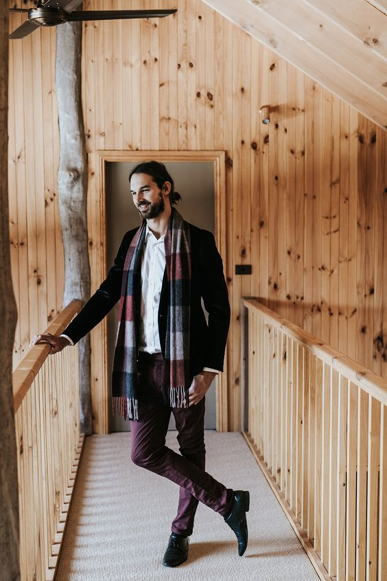 a casual and comfy winter groom's look with a black velvet blazer, burgundy pants, a white button down and a bright scarf