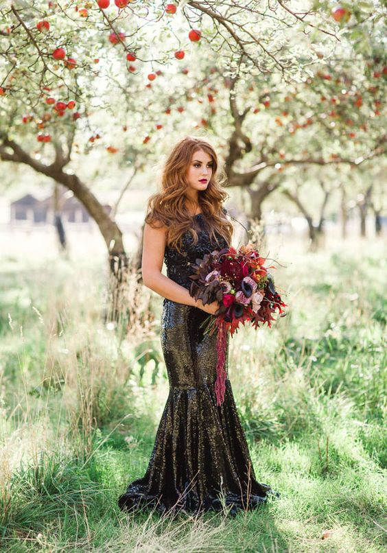 a black sequin mermaid wedding dress with a lace bodice and a bright berry-hued wedding bouquet
