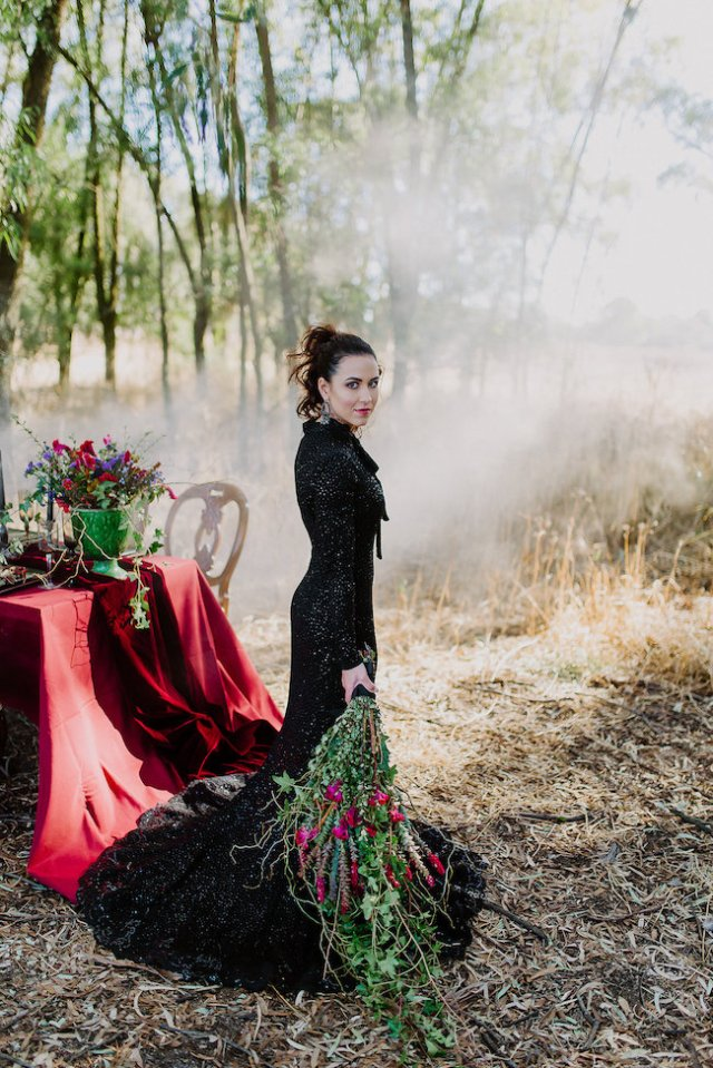 a black sparkling mermaid wedding gown with a high neckline, long sleeves and a train