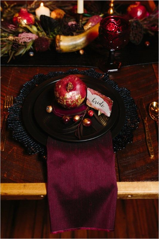 a bold place setting with black plates and a charger, a burgundy napkin and a gilded pomegranate