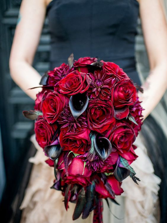 a cascading wedding bouquet of black callas and deepr red roses is ideal for a Halloween bride