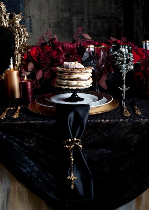 a gorgeous soft gothic wedding tablescape with a black lace tablecloth, a black napkin, gilded plates and lush deep red florals on the table