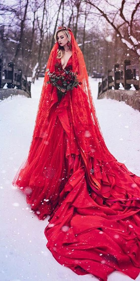 a hot red wedding ballgown with a plunging neckline and a train,, a matching veil and a crown plus a red lip