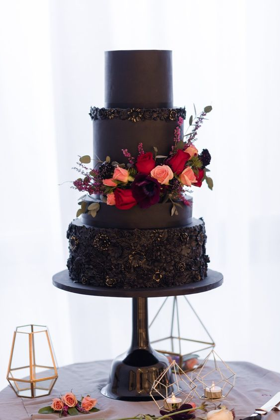 a modern black wedding cake with textural tiers, red and peachy flowers for decor