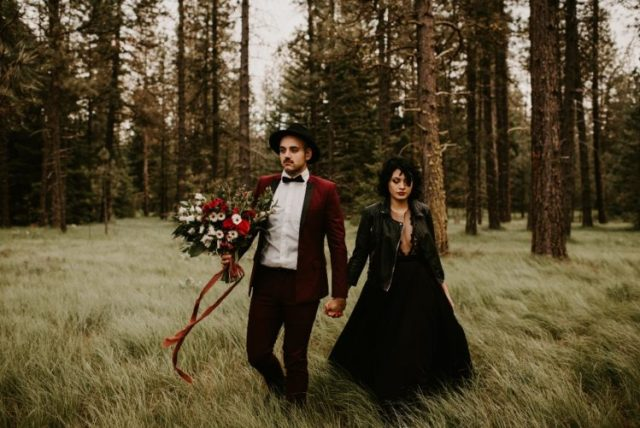 the bride rocking a black wedding ballgown with a sheer bodice, the groom wearing a deep red tux with black lapels