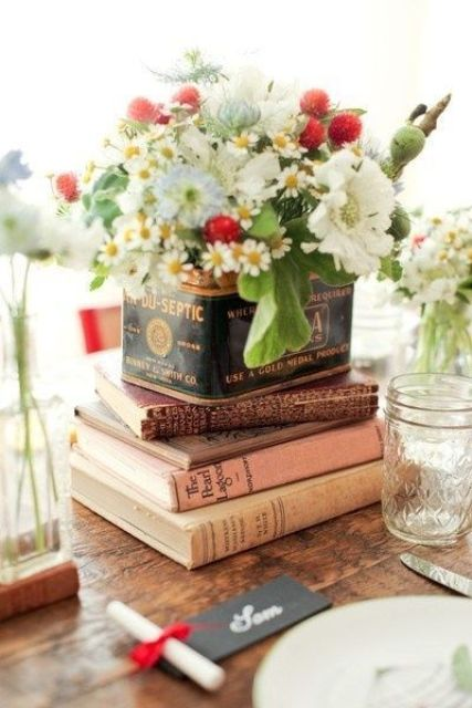 a bright summer wedding centerpiece with books, a vintage tin can and fresh blooms in it