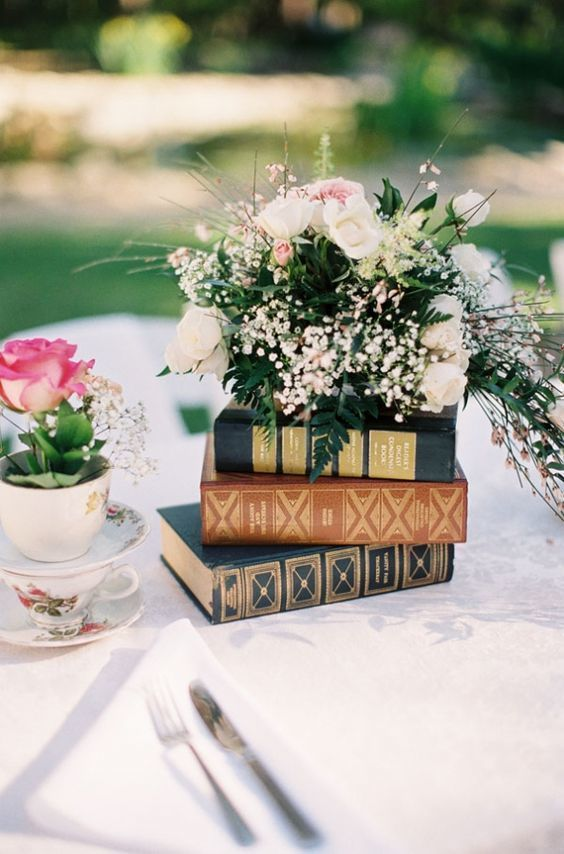 a stack of books plus a lush floral arrangement on top is a beautiful garden wedding centerpiece idea