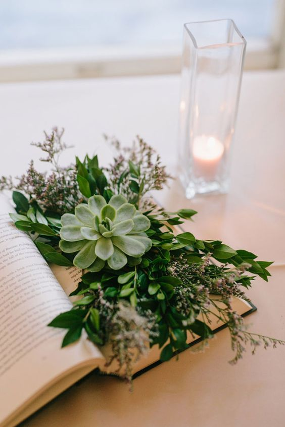 an opened book with lush greenery, blooms and a large succulent is a chic and refreshing centerpiece idea
