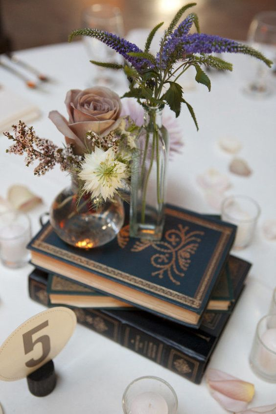 navy books, two clear vases with simple blooms and a single dusty pink rose for a beautiful look