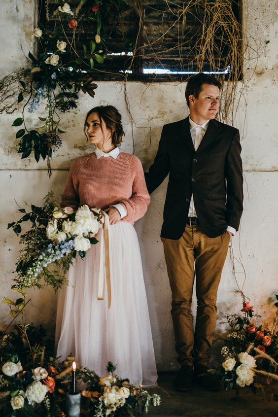 a peachy pink sweater over a pink high neckline wedding dress for a colorful touch