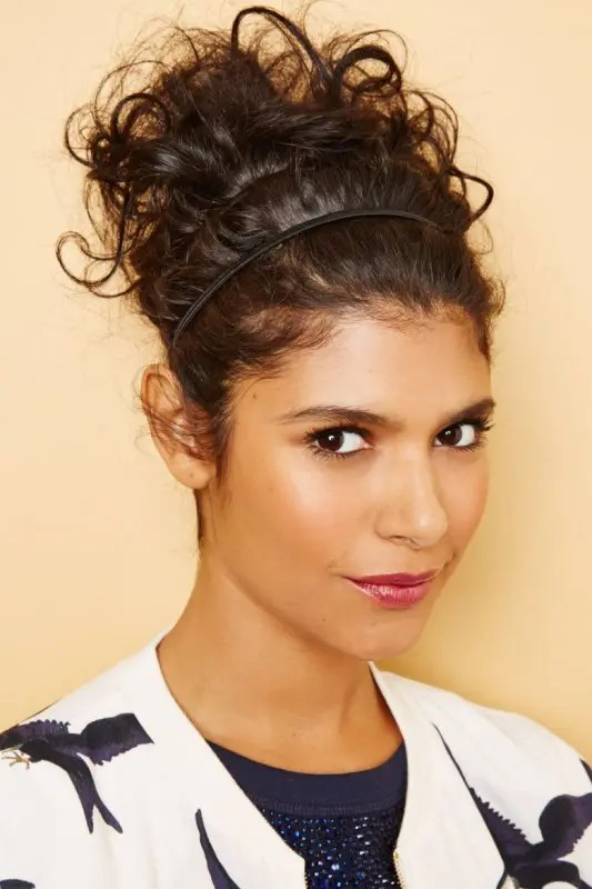 a curly updo with a hair vine to keep it in place is a cool casual option