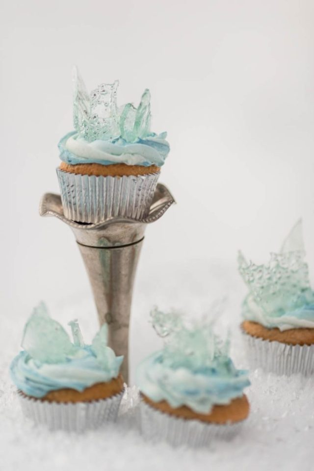 Frozen-themed wedding cupcakes with blue icing and clear blue shards on top look fantastic