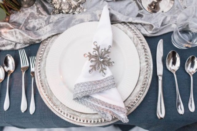 a Frozen inspired place setting with a silver charger, a lace trim napkin plus a rhinestone snowflake as a napkin ring