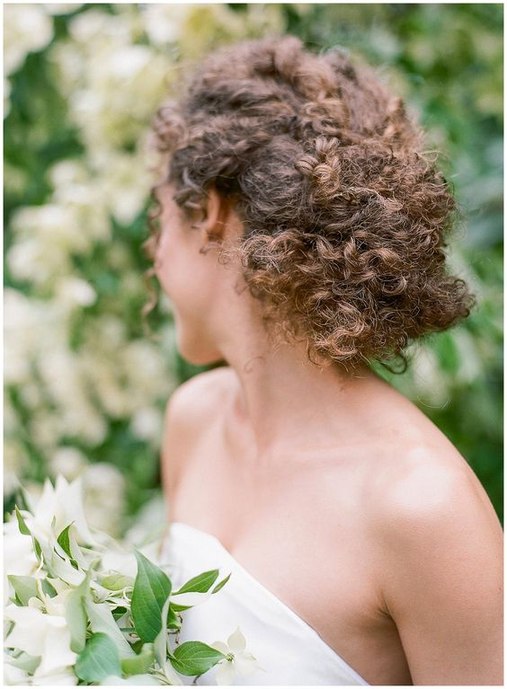 a braided low updo with natural curls is a chic textural idea that will make a statement in your look