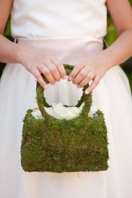 a moss purse-shaped flower girl basket with white petals is a unique idea for a wedding